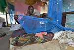 Mou Leu Chol covers her 2-year old son Yuel with a tattered mosquito net in Bor, a city in South Sudan's Jonglei State that has been the scene of fierce fighting in recent months between the country's military and anti-government rebels. After fighting broke out in mid December 2013, control of the town changed hands four times in a few weeks. ACT Alliance members were among the first humanitarian agencies to enter the city in January 2014, and are providing services to thousands of people who are cautiously returning home to the troubled city. Chol came to Bor in March 2014 to escape continued fighting in nearby Duk County. She and her husband assembled their new home out of the scraps of building materials they found here. She will soon replace her old mosquito net with a new one she received in a household package given to her by Dan Church Aid and the Lutheran World Federation, both members of the ACT Alliance. The package also contained plastic sheeting, cooking pots, a machete, mats, and other essential items.