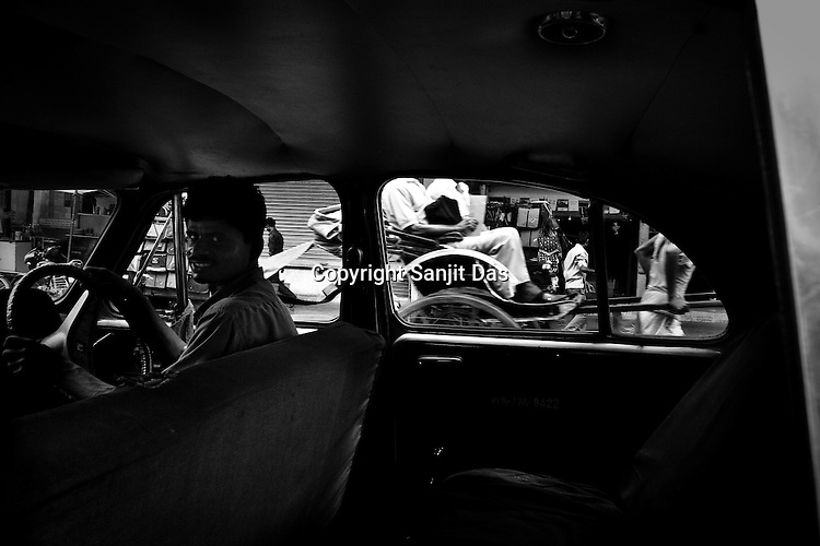 A hand pulled rickshaw drives past while the taxi driver smiles for the photographer in Calcutta, India.