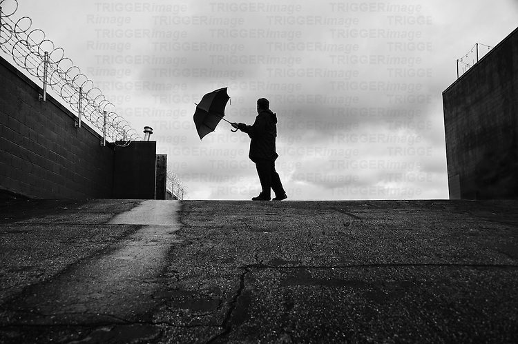 Silhouetted man holding an umbrella with outstretched arm at top of hill with barbed wire fencing.