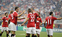 Jonny Evans #23 and John O'Shea #22 of Manchester United congratulate Fredrico Macheda #27 after his second goal during the 2010 MLS All-Star match against the MLS All-Stars at Reliant Stadium, on July 28 2010, in Houston, Texas. Manchester United won 5-2.