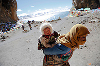 A Tibetan woman carries a child as they visit Namtso lake in the Tibet Autonomous Region, China November 18, 2015. Located four hours' drive from Lhasa at an altitude of around 4,718m (15, 479 ft) above sea level, Namtso lake is not only the highest saltwater lake in the world but also considered sacred attracting throngs of devotees and pilgrims. REUTERS/Damir Sagolj