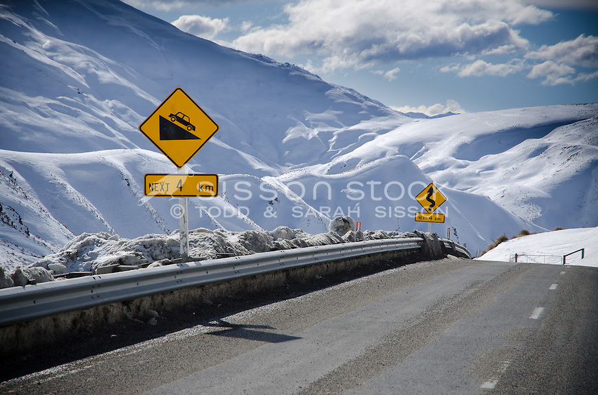 Steep grade and winding road signs on the treacherous Crown Range road between Queenstown and Wanaka. Winter time, snow and grit on road,  Sunny day looking down Cardona valley.