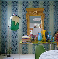 A modern table and designer floor lamp are juxtaposed against a baroque wallpaper in the dining room