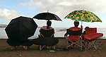 Ladies stay shaded under umbrellas as they take in canoe races along Hilo Bay on the Big Island, Hawaii.