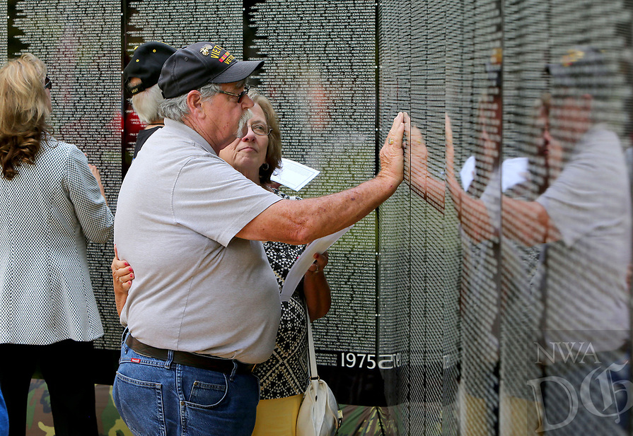 NWA Democrat-Gazette/DAVID GOTTSCHALK  Linda Evans comforts her husband Vietnam War and Marine Corp Veteran David Evans locate the name Thursday, May 18, 2017, as he reflects on a  friend's name on the Vietnam Veterans Memorial The Moving Wall following opening ceremonies on the campus of the Veterans Health Care System of the Ozarks in Fayetteville. The wall has been touring the country for more than 30 years and will on the camus through Monday, May 22. The Moving Wall is a half scale replica of the memorial in Washington D.C..