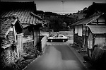 A heavy police presence in the veritable ghost town of Kawauchi Village, which sits right on top of the 20 km (12.4 miles) nuclear no-entry zone line, and the police check point is less than 100 m to the left.  Less than two weeks ago, this half of the village was within the exclusion zone but the police check point has been moved back to the edge of the village.  It still sits within the 30 km (18.6 miles) voluntary evacuation zone where residents are encouraged to stay indoors and be ready for immediate evacuation if necessary.  Important crossroads between Koriyama in the main central valley and Iwaki a seaside harbor town, pass through this isolated mountain village.  Some villagers have begun to return but the village remains a ghost town.   Fukushima Prefecture, Japan.