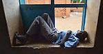 A boy relaxes in a window at the John Paul II School in Wau, South Sudan.