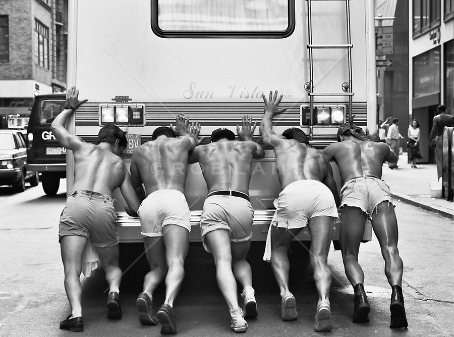 shirtless men pushing a van in New York City