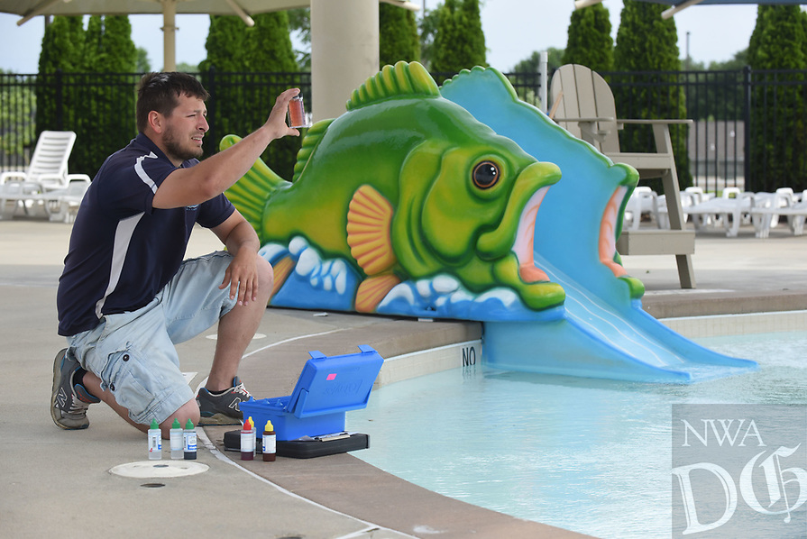 NWA Democrat-Gazette/FLIP PUTTHOFF <br />TESTING THE WATERS<br />David Henson, maintenance supervisor at the Rogers Aquatics Center, tests water Wednesday May 17 2017 at the various pools at the center on South 26th Street in Rogers. The aquatics center will open at 11 a.m. on May 27. A one-half price sale on passes to the center goes on through May 26, Henson said. A pass is good for 10 admissions. They may be purchased at the center's admission office or at www.rogersaquaticscenter.com.