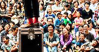 Lots of laughing & smiling faces enjoying street entertainment in Tokyo.
