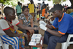 Said Innocent Tologo draws blood from a woman for a rapid HIV test in Nimule, South Sudan, during a mobile clinic run by Caritas of the Diocese of Torit. Reenae Anuor Ondiek, another clinic worker, looks on. The mobile clinic was launched in January 2014 shortly after war broke out within South Sudan, and thousands of families arrived in this area, near the country's border with Uganda, from Bor, in Jonglei State. Yet many have not been warmly welcomed to this region of Eastern Equatoria State, where two earlier waves of displaced people in the 1980s and 1990s left relations tense between the newcomers, who are Dinka, and the largely Ma'adi residents around the city of Nimule. The ACT Alliance is helping the displaced families and the host communities affected by their presence, and is supporting efforts to reconcile the two groups. The ACT Alliance also supports the Caritas mobile clinic, which provides medical care--often under a tree--both to displaced families as well as to poor residents of the host communities.