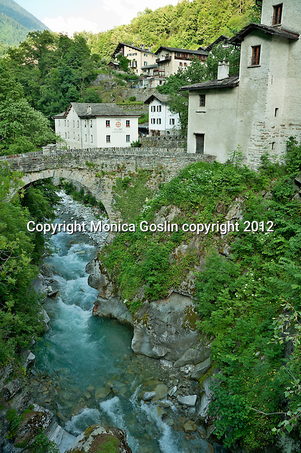 Houses and an old Roman Bridge in the small town of Promotogno in the Swiss valley of Bregaglia in the Graubunden Canton of Switzerland