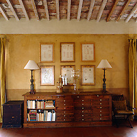 The fifteen foot high ceiling of this Tuscan living room has been lowered visually by painting the walls in broad horizontal bands in varying tones of ochre and sand