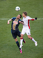 Sebastien Le Toux (11) of the Philadelphia Union goes up for a header with Scott Caldwell (6) of the New England Revolution during the game at PPL Park in Chester, PA.  The Philadelphia Union defeated the New England Revolution, 1-0.