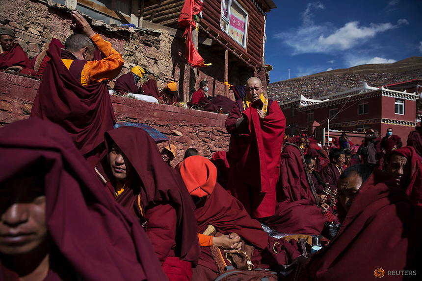 Tibetan Buddhist monks pray at Buddhist laymen lodge where thousands of people gather for daily chanting session during the Utmost Bliss Dharma Assembly, the last of the four Dharma assemblies at Larung Wuming Buddhist Institute in remote Sertar county, Garze Tibetan Autonomous Prefecture, Sichuan province, China October 30, 2015. The eight-day gathering of people chanting mantras and listening to teachings of monks starts every year around the 22rd of the ninth month on Tibetan calendar, the great day of Buddha's Descending from Tushita Heavens. The Larung Wuming Buddhist Institute, located some 3700 to 4000 metres above the sea level was founded in 1980 by Khenpo Jigme Phuntsok, an influential lama of Nyingma sect of Tibetan buddhism with only around 30 students but is now widely known as one of the biggest centres to study Tibetan Buddhism in the world. Picture taken October 30, 2015.  REUTERS/Damir Sagolj