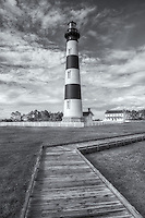 An early morning view of the Bodie Island lighthouse and adjacent boardwalk under a partly cloudy sky in Cape Hatteras National Seashore in the Outer Banks of North Carolina.
