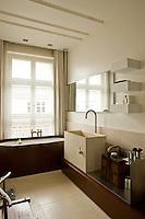 The bathroom features a deep stone wash basin and a wood-encased bath