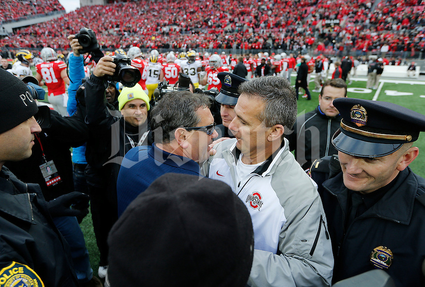 Ohio State Buckeyes head coach Urban Meyer, right, shakes hands with Michigan Wolverines head coach Brady Hoke, left, after the college football game between the Ohio State Buckeyes and the Michigan Wolverines at Ohio Stadium in Columbus, Saturday morning, November 29, 2014. The Ohio State Buckeyes defeated the Michigan Wolverines 42 - 28. (The Columbus Dispatch / Eamon Queeney)