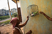 A parrot is fed by his owners in Belgharia township outside of Dhanbad in Jharkhand, India. Families from various villages with underground fires have been rehabilitated in Belgharia township. Photo: Sanjit Das/Panos