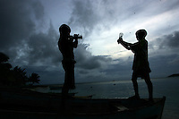 Two boys play with empty bottles in Cayos Cochinos near Chachauate Cay, Honduras on August 10, 2007..Born in Argentina, photographer Ivan Pisarenko in 2005  decided to ride his motorcycle across the American continent. While traveling Ivan is gathering an exceptional photographic document on the more diverse corners of the region. Archivolatino will publish several stories by this talented young photographer..Closer look at  Ivan's page www.americaendosruedas.com....
