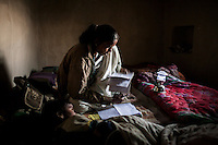 Shanti Adivasi, 52, works without electricity with her interview notes as she does every evening on a row of beds she shares with her family of 14 in Manikpur, Chitrakoot, Uttar Pradesh, India on 4th December 2012.  Shanti used to be a wood gatherer, working with her parents since she was 3, and later carrying up to 100 kg of wood walking 12km from the dry jungle hills to her home to repack the wood which sold for 3 rupees per kg. After learning to read and write in an 8 month welfare course, at age 32, she became a reporter, joining Khabar Lahariya newspaper since its establishment in 2002, and making about 9000 rupees per month, supporting her family of 14 as the sole breadwinner. Photo by Suzanne Lee for Marie Claire France.