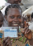 Sarasia Emilio Anisie shows her new registration card and a finger she dipped in ink as she finishes the registration process to vote in in the January 2011 referendum on whether Southern Sudan will secede from the north of the country. In the Kopoita neighborhood of Nzara, in Western Equatoria State, this registration center was established for people who've been internally displaced by attacks from the Lord's Resistance Army. The vote on the referendum was over 98 percent in favor of independence. NOTE: In July 2011 Southern Sudan became the independent country of South Sudan.