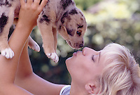 Photo of a woman holding a puppy up over her head and giving it a kiss.