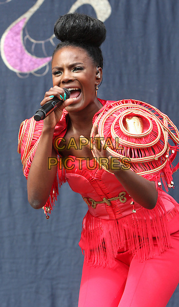 Shingai Shoniwa.THE NOISETTES perform at Day Two V Festival at Hylands Park, Chelmsford, Essex, England..August 21st, 2011.stage concert live gig performance music half length red pink trousers top jacket epaulettes shoulder pads gold fringed tassels singing hair up bun .CAP/ROS.©Steve Ross/Capital Pictures