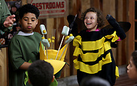 NWA Democrat-Gazette/DAVID GOTTSCHALK  Chris Anderson (left) and Aleana Gray-Smith, both third grade students at Leverett Elementary School, are dressed as a flower and bee Wednesday, March 15, 2017, as they illustrate the process of pollination with entomologist Sim Barrow (not pictured), with the Northwest Arkansas Land Trust, at the Kessler Mountain Outdoor Classroom & Nature Center in Fayetteville. The students were their science curriculum. The visit also included a hike