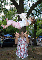 A father throws his child in the air during the annual Inman Park parade in Atlanta, Georgia.