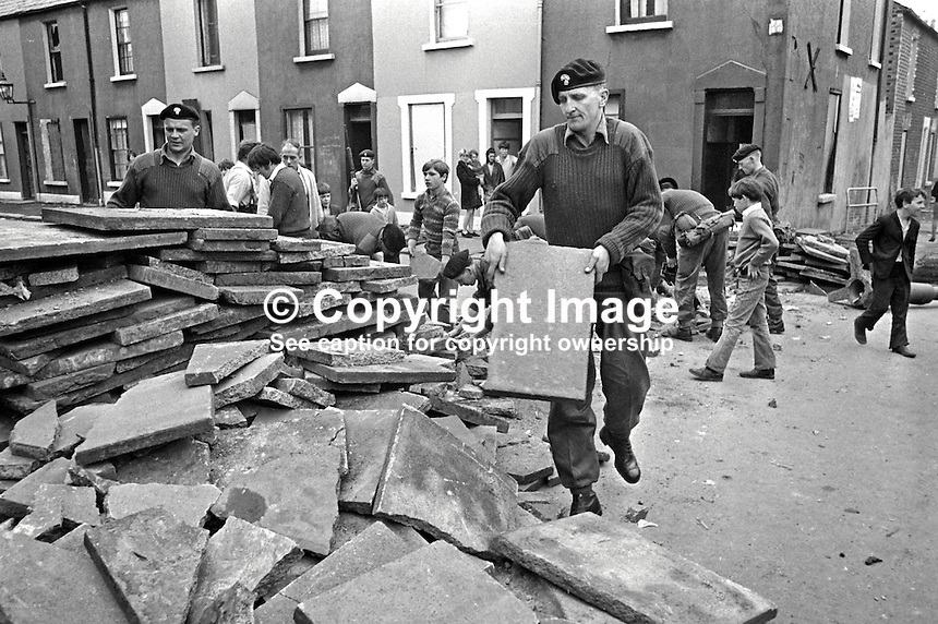 Troops, with some assistance from local residents, removing one of a number of barricades in the Lower Falls Road area of Belfast, N Ireland. 196009160250a, 250/69.<br />