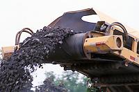 Asphalt Debris Ejected from Cold Planer on Road Preparation