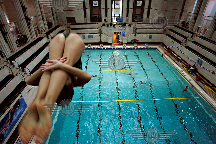A diver takes the plunge from the high-dive at the swimming pool in the Soviet-built Palace of Culture.