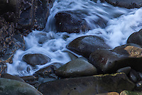 Waves flowing onto rocks at Bean Hollow State Beach are softened and blurred by slow shutter speed.