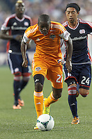Houston Dynamo midfielder Boniek Garcia (27) dribbles as New England Revolution midfielder Lee Nguyen (24) defends. In a Major League Soccer (MLS) match, Houston Dynamo (orange) defeated the New England Revolution (blue), 2-1, at Gillette Stadium on July 13, 2013.