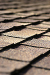 Curled roofing shingles photographed as a repeating pattern.