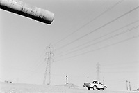 Iraq. Baghdad. Waste of the war. A white Toyota pick-up van drives on Mossul road, passing near a destroyed iraqi tank shot by air strikes attacks from the coalition forces (American army). © 2003 Didier Ruef