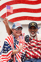 Wearing the flag and waving the flag, spectators at the 2015 Veteran's Day Parade in downtown Houston pose for photos on one of the floats.