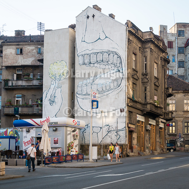 Art-mural on side of an apartment building showing an open mount of teeth composed of buildings and holding a tree ready to eat like a stalk of broccoli. Public art and architecture in downtown Belgrade, Serbia<br /> <br /> Artwork by Blu