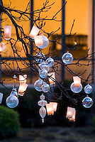 Glass baubles and tealights hanging from a tree in the courtyard make a beautiful and atmospheric display