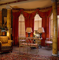 This bay window is furnished with a painted bamboo sofa and chairs and framed by a pair of marbleised columns and elaborate red silk curtains