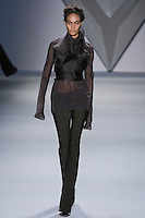 Joan Smalls walks runway in a brown organza multi-layer flange harness over brown silk chiffon long sleeve top, and brown techno stretch flared pant from the Vera Wang Fall 2012 Vis-a-gris collection, during Mercedes-Benz Fashion Week Fall 2012 in New York.