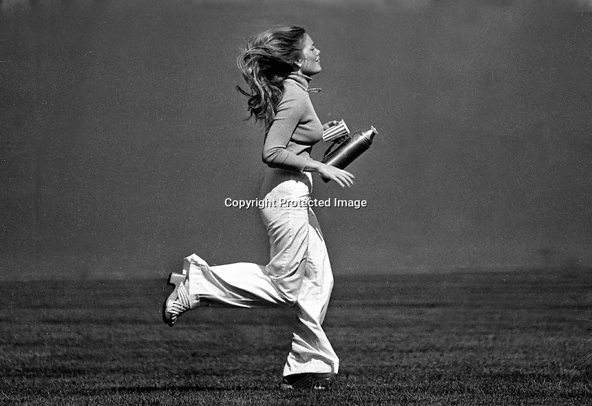 Oakland A's ball girl...Debbie Sivyer AK (Mrs. Fields)runs to deliver water to outfield umpire.(photo 1972 Ron Riesterer)