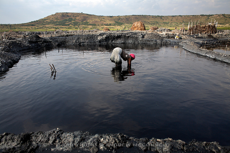 A woman scrapes salt from the bed of a pan at Lake Katwe, Uganda. Those who do not own their own salt pan work in other pans for a wage of almost $1 a day.