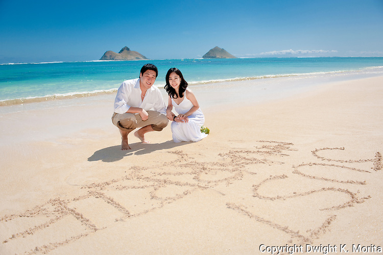 """Asian bride and groom pose with with their """"Just Married"""" sign in the sand during a stroll on Lanikai beach."""