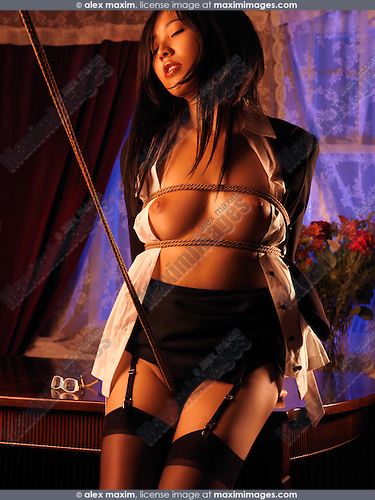 Asian Woman Standing At A Table Tied Up With Japanese Rope Bondage