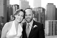 Black & white portrait of bride and groom on terrace with NYC skyline in background.
