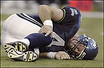 Seahawks quarterback Trent Difler lies on the field and grabs his right knee after being hit by Indianapolis Colt defenders James Cannida and Chad Bratzke early on the second quarter on Saturday, Aug., 10, 2002. The Colts beat the Seahawks 28-10 in the preeason game. (AP photo/Jim Bryant)