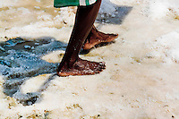 A Colombian barefoot man works in the salt mines of Salinas de Manaure, Colombia, 12 May 2007. Manaure, the arid region in northern most part of South America (Guajira Peninsula), with its very hot and dry climate throughout the year and with the naturally formed lagoons, has always been favorable for the salt production. The salt explotation, run in this area by the Wayuu Indians and later by Colombian mestizos, is known since the pre-Columbian era. Although nowadays the salt production reach to one million tons a year, processed both by industrial and artisanal methods, no social or economical development has been marked in the local community. Sea salt industry in Manaure covers the major part of Colombia's salt consumption.