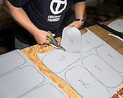 Matthew Tunney cuts out material for the interior of the ELF model, Organic Transit, Durham, N.C., Friday, May 24, 2013